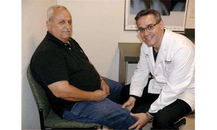 Jose Marina, D.O., examines the knee of patient Pedro Cantu during a consultation